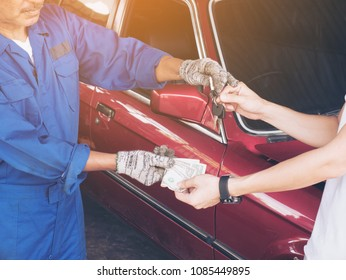 Car key in hand and cash money in other hand of bill,  Money to repair the car. Financial concept.