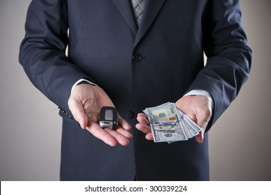 Car key and hundred-dollar bills in the hands of a businessman on a gray background