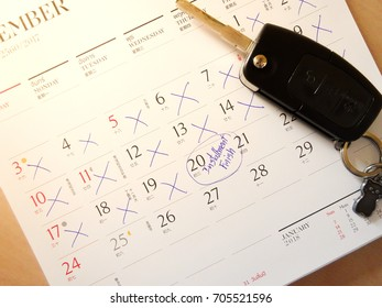 Car key on white Thai calendar on wood desk and made circle marked on date to mark appointment reminder of installment pay for car finance.