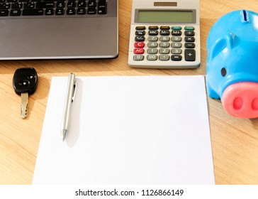 Car key and pen with paper notepad and piggy bank , calculator and labtop computer on wood table desk