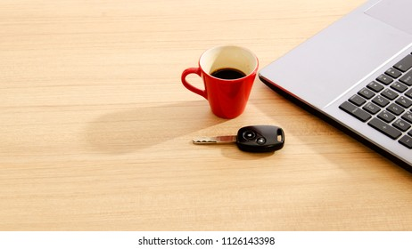 Car key and Red coffee cup and labtop on wood table backgrounds