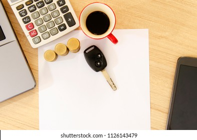 Car key and red cup coffee with office supplies on wood table desk backgrounds above