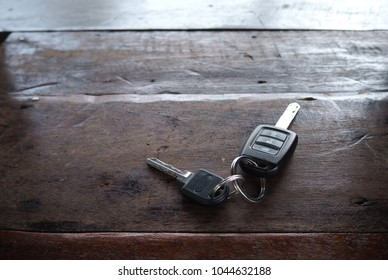 Car key with remote control on the wood table.