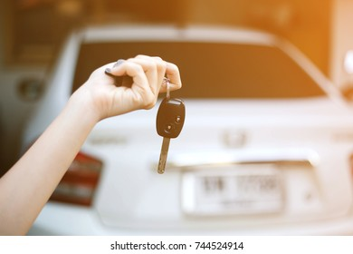 Car key in woman's hand with car in background and sunlight.