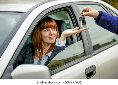 car keys handover. young woman sitting in car smiles as dealer hand over keys. concept of car rental car sharing or automobile business
