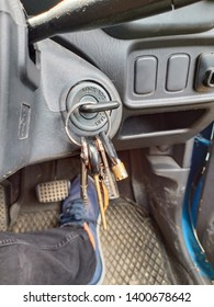 car keys ignition with foot and dashboard background -image