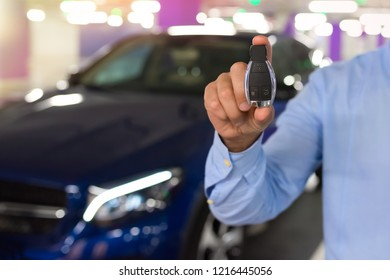 Car Keys. Male hand holding car key, on a parking background