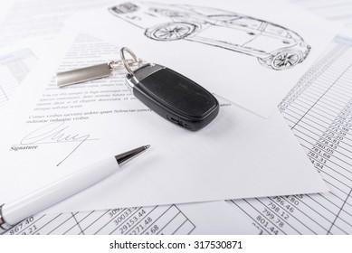 Car keys on the signed agreement document (random latin dummy text used)