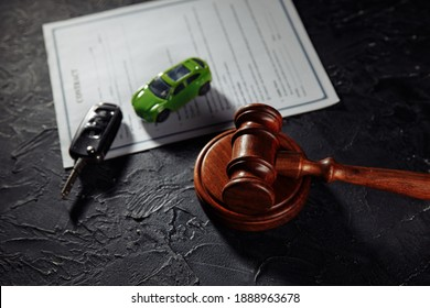 Car with keys and wooden judge gavel. Concept of selling a car by auction or accident sentence