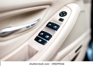 car leather interior details of door handle with windows controls and adjustments. Car window controls