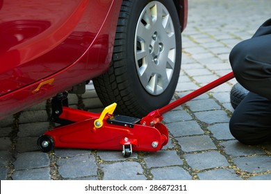 Car Lifted With Red Hydraulic Floor Jack For Repairing