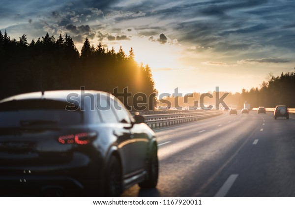 Car and light on the evening road. Sunset