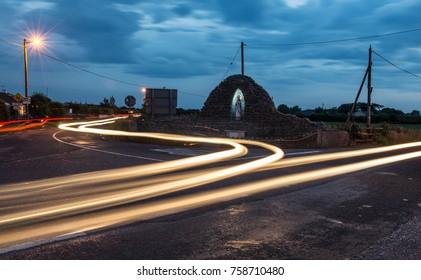 Car light streaks  on a holy crossroads in rural Ireland