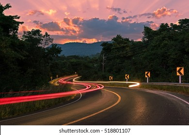 Car Light trail on Long macadamized S-curvy road with trees and beautiful twilight sky and sun through clouds at twilight time: countryside Thailand