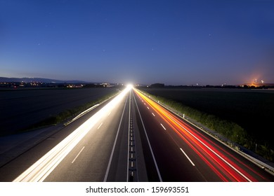 Car light trails at night on highway.