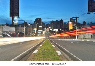 Car light trails on an avenue in Campinas, SP/ Brazil at night with buildings in the background