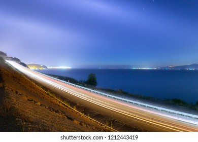 Car lights and coastal path at sea shore. Car lights on the road near the coast. Coastal highway. Istanbul, Turkey