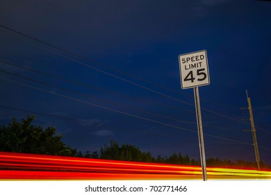 Car Lights Fly Past Speed Limit Sign
