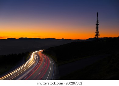 Car lights at night towards the city and communications antenna