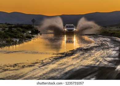 A car with the lights on splashing water while crossing a puddle made by the recent rains on a dirt road at Atacama Desert at dusk with amazing reflections of the orange colors from a sunset sky