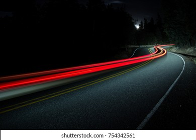 Car lights streaking through the night on a mountain road