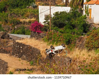 A car, limousine has fallen headlong down the slope and is located on the roof, in the midst of a terraced cultural landscape on La Gomera