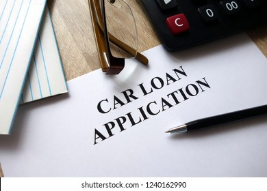 Car loan application form with pen, calculator and glasses on desk