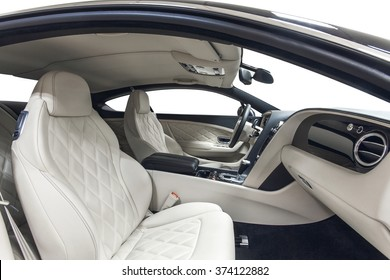 Car luxury inside. Interior of prestige modern car. Front seats with steering wheel. White cockpit with on isolated white background.