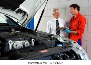 Car mechanic in auto repair garage with customer beside car