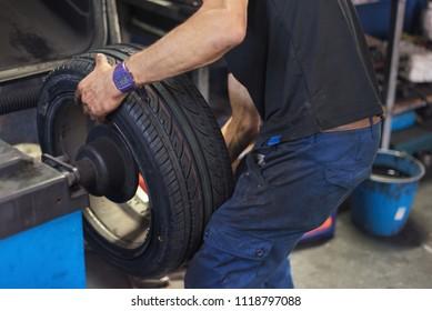 Car mechanic balancing car wheel