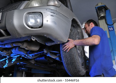 Car mechanic changing flat tire - a series of MECHANIC related images.