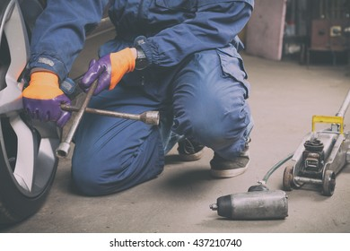 Car mechanic changing tire in the service.