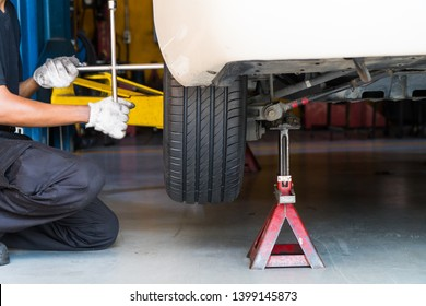 A car mechanic changing tyre and tightening screw with 4 way lug wrench.