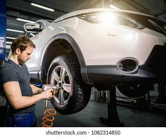 car mechanic changing car wheel in auto repair garage