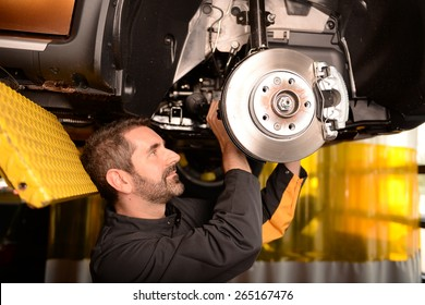 Car mechanic checking car at auto repair shop service station, front or rear axle inspection