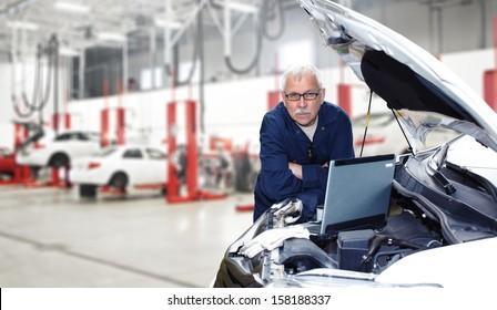 Car mechanic checking engine. Auto repair service.