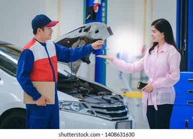 The car mechanic is delivering the car keys to the young women who bring the car to repair in the car repair shop and the customers are happy in the service of the staff and are satisfied with the rep