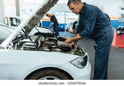 Car mechanic with diagnostic device for reading the error codes. Mechanic checking the car in service station.