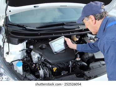 A car Mechanic with diagnostic equipment tablet
