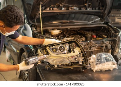 Car mechanic, doing cleaning, The headlight of the car, installation and turning headlight of modern automobile and car projector lens. Vehicle head xenon lamp in details.