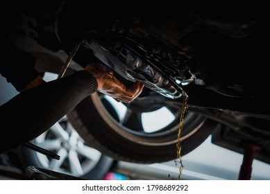 Car mechanic drain the old automatic transmission fluid (ATF) or gear oil at car garage for changing the oil in a gear box of car engine