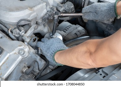 The car mechanic is exerting a long handle torque wrench with a glove-wearing hand to repair and maintain the engine of the car.