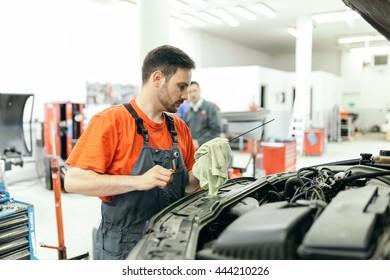 Car mechanic fixing a car in garage at dealership