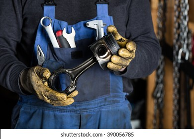 Car mechanic in garage with old car engine piston. Concept
