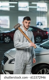 Car mechanic with a hammer