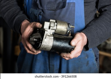 Car mechanic hand holding Old car starter gear, part of engine starter motor at repair service. Garage concept