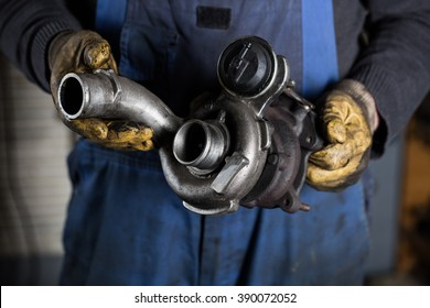 Car mechanic hands in garage with old and used turbocharger. Turbine Concept