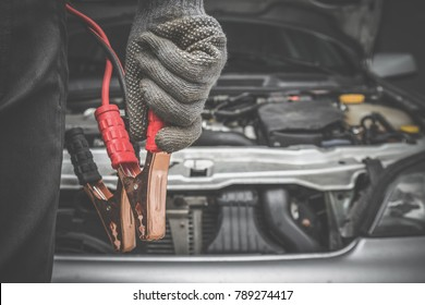 Car mechanic hands in gloves is ready charging a discharged battery with booster jumper cables in the garage. Problems and solutions concept. Cares about automobile.