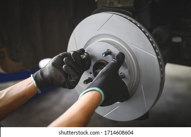 Car mechanic hands installing new six slot brake discs.