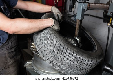 Car mechanic hands replace tires on wheels in garage. Mechanic technician worker installing car wheel at maintenance. Tire installation concept